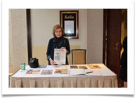 Dr. Ramsey at the reception table with a copy of the invitation/flyer